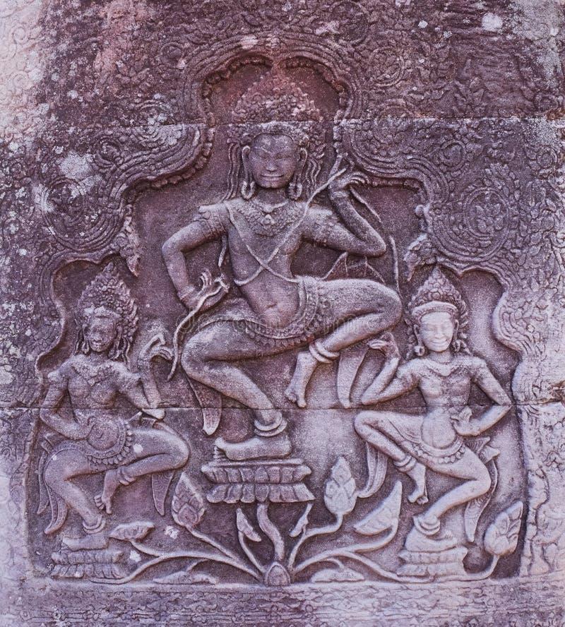 Forntida stena basrelief på väggen av en övergiven en khmertempel Stenskulptur av tre dansa kvinnor fotografering för bildbyråer