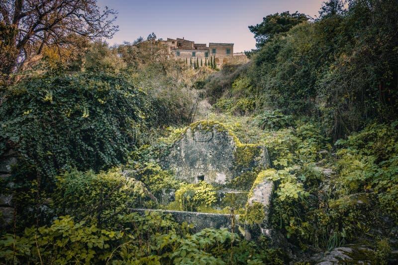 Forntida stena vattenho på Costa i Korsika arkivfoton