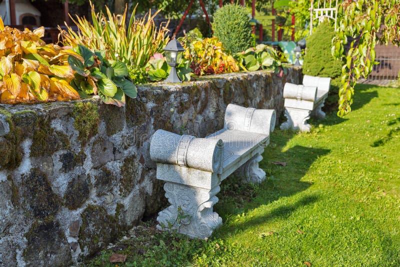 Forntida stenbänk i en trädgård royaltyfri bild