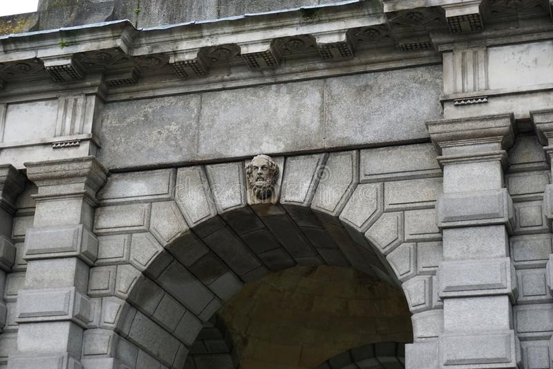 Forntida stenbåge med den sned stenbysten i Dublin Ireland royaltyfri foto