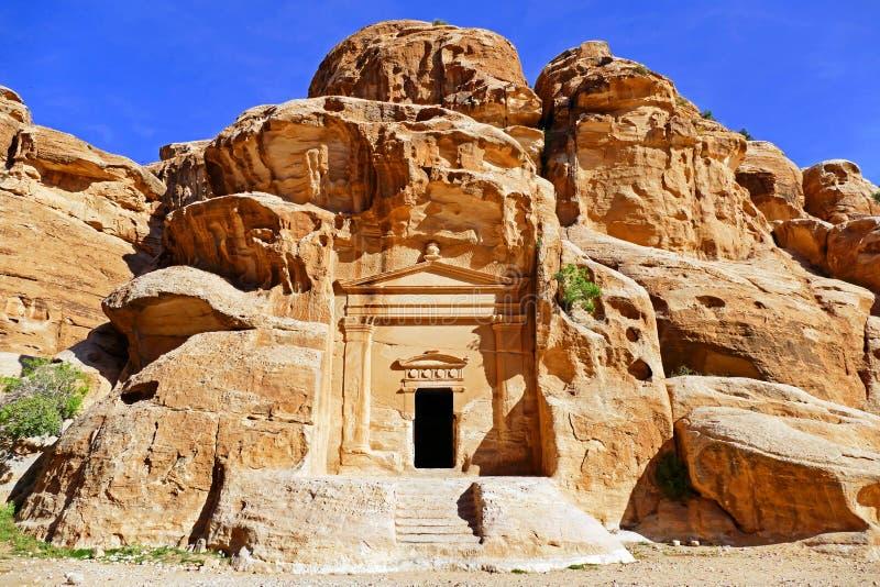 Forntida stenCarvingsingång av liten Petra, Jordanien arkivbild