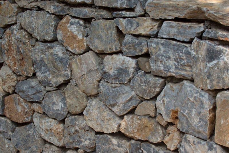 Forntida stenvägg av fästningen Murverk av gamla stenar och tegelstenar ovanlig bakgrund royaltyfri fotografi