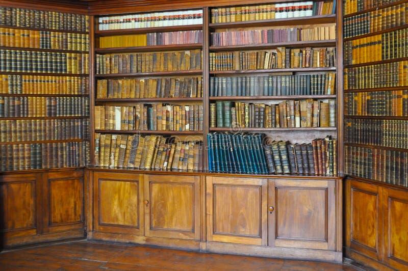 Forntida träbokhyllor med den dammiga bokhyllan för gamla arkivböcker med samlingen för sällsynta böcker i Retro arkiv för bokhyl royaltyfri fotografi