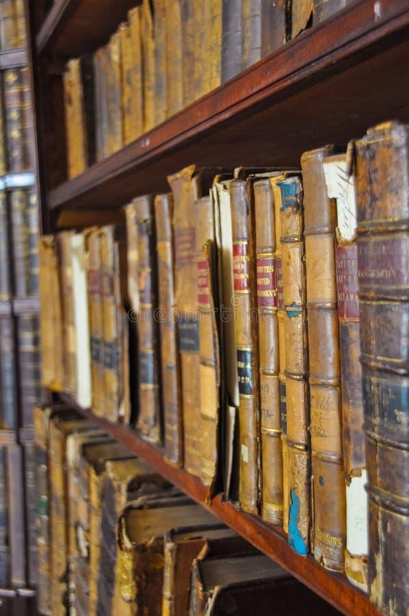 Forntida träbokhyllor med den dammiga bokhyllan för gamla arkivböcker med samlingen för sällsynta böcker i Retro arkiv för bokhyl arkivfoton