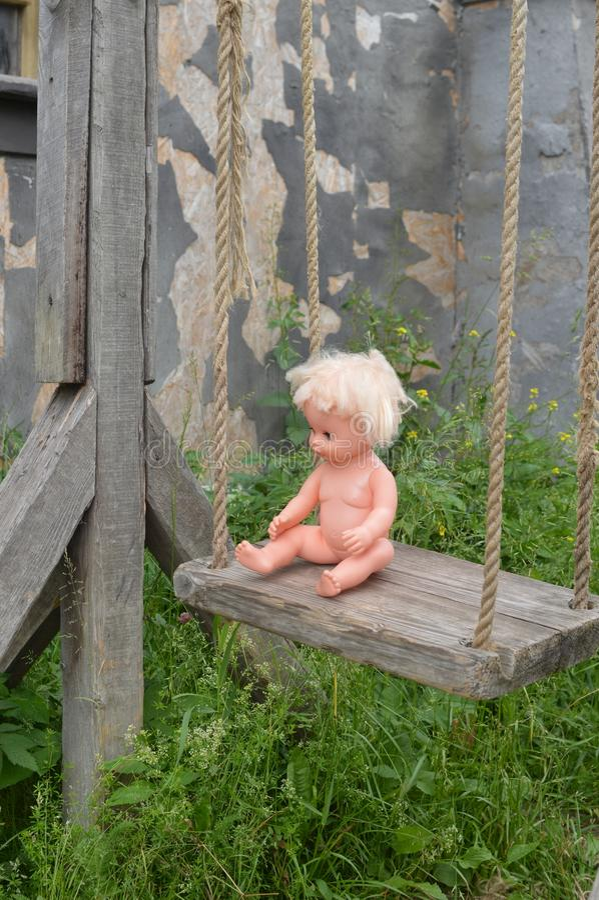 Forntida trägunga på rep En plast- naken docka på en gunga royaltyfri foto