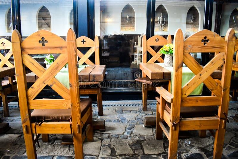 Forntida trästolar med medeltida garneringar i tappningrestaurang med många feodala ålderdekorbeståndsdelar arkivbild