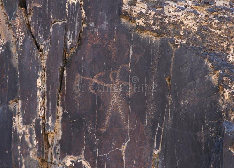 Forntida vagga teckningar, människa med pilbågen och pilen som jagar arkivfoton