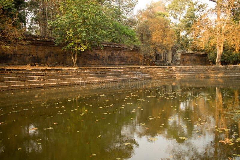 Forntida vattenpöl vid en bruten vägg i Angkor Thom, Cambodja arkivbilder