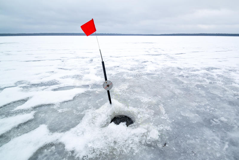 Foro del ghiaccio in pesca e barretta di inverno immagini stock libere da diritti