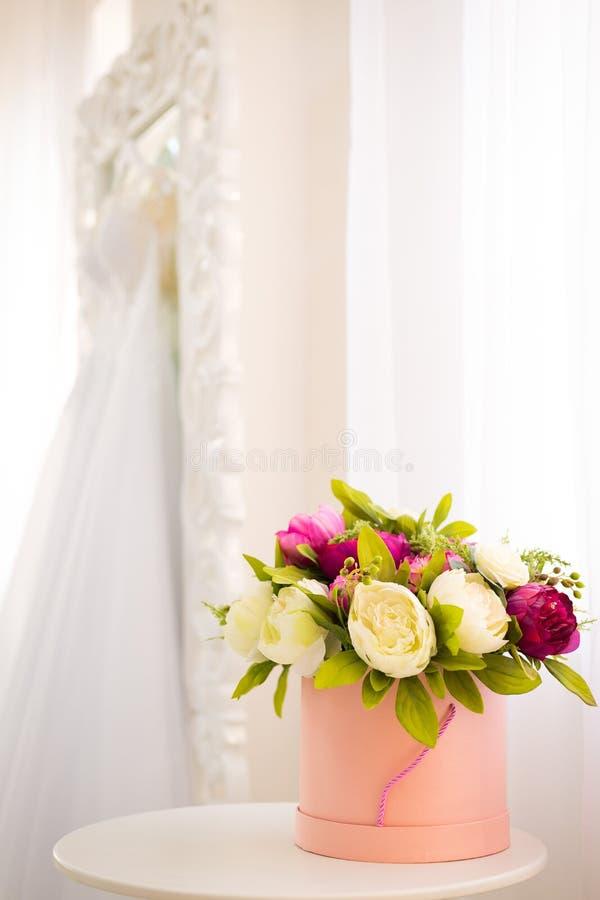 Foro di colore rosa rotondo, all'interno di peonie colorate sullo sfondo di uno specchio bianco con abito da sposa fotografia stock
