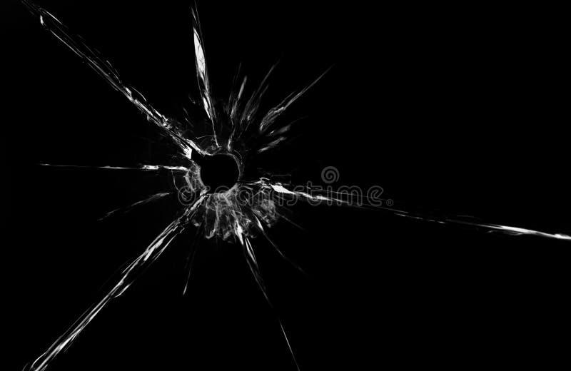 Foro di pallottola nella fine di vetro su su fondo nero immagini stock
