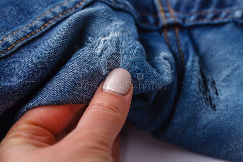 Foro e fili sui jeans del denim Fondo lacerato distrutto strappato delle blue jeans Chiuda su struttura blu del tralicco fotografia stock