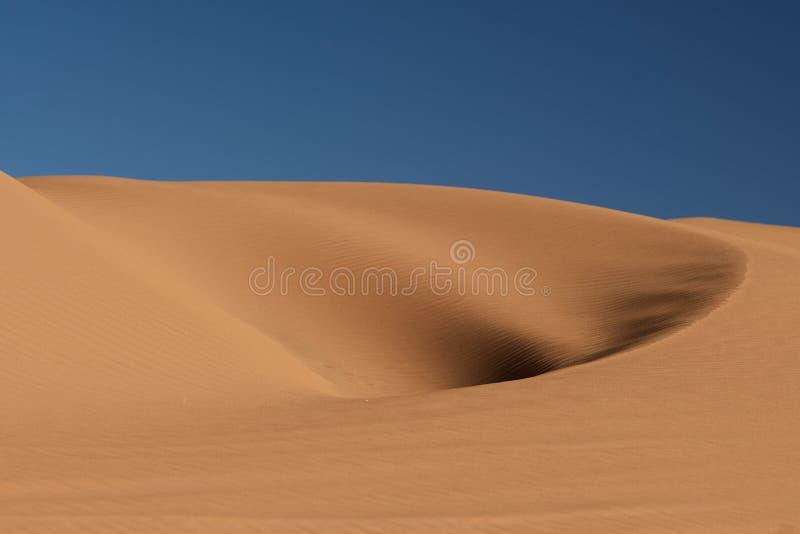 Foro nella duna sotto il cielo blu fotografia stock