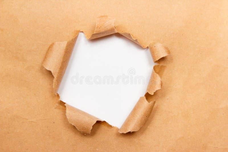 Foro nello strato marrone della carta del mestiere con i bordi lacerati Centro bianco isolato, percorso di ritaglio incluso Vista immagine stock