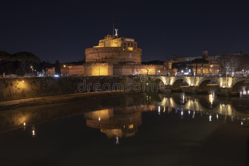 Foro romano del Th Hermosa vista de Castel Sant 'Ángel y el puente en la noche con reflexiones en el río de Tíber fotografía de archivo