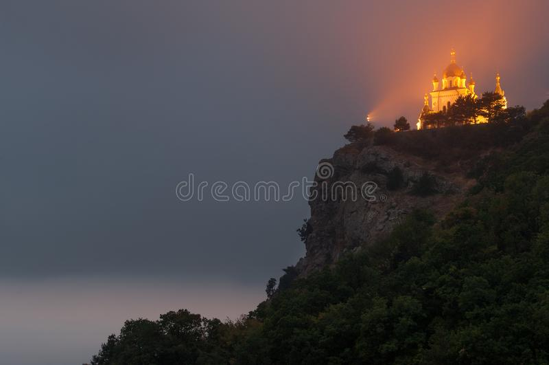 Foros church near Baydar Pass. Popular scenic Church of Christ Resurrection on the cliff above Black Sea coastline near Foros, Crimea, illuminated at dusk royalty free stock photography