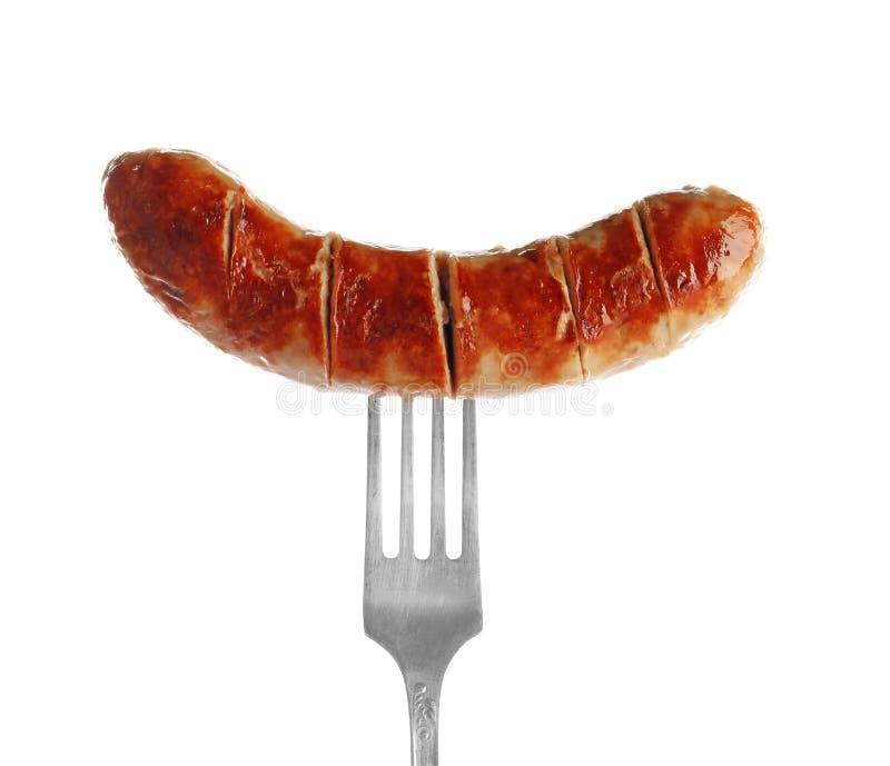 Forquilha com a salsicha grelhada deliciosa no fundo imagem de stock royalty free