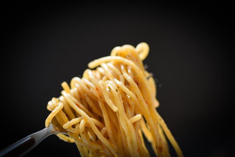 Forquilha dos espaguetes no fundo preto escuro - massa italiana clássica apetitosa saboroso dos espaguetes do alimento delicioso  imagem de stock royalty free