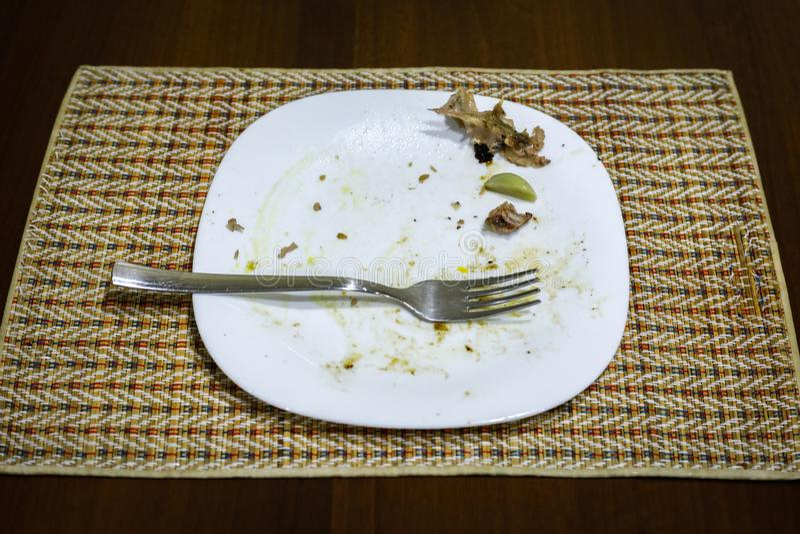 Forquilha e alimento restante em uma placa imagens de stock