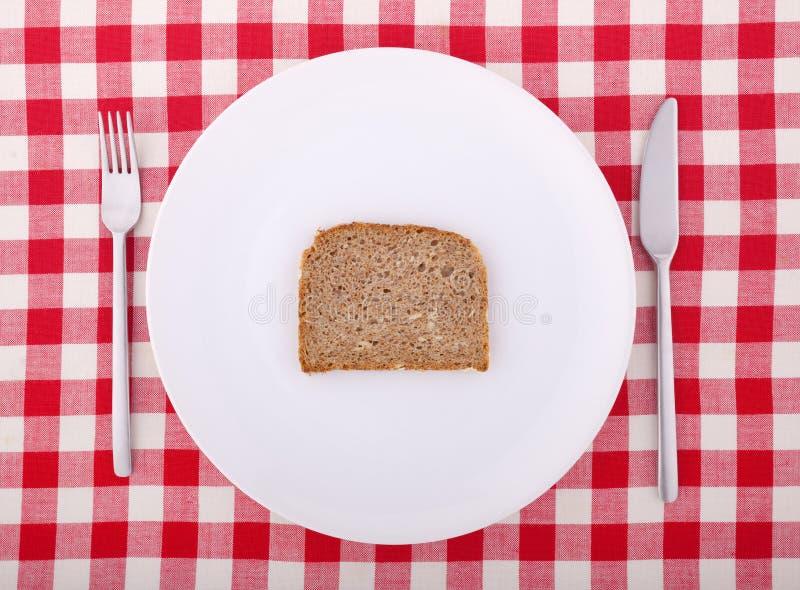 Forquilha, faca e uma fatia de pão em uma placa fotografia de stock royalty free