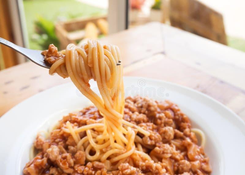 A forquilha rola acima os espaguetes Espaguetes com molho de tomate da carne de porco Doce fotos de stock royalty free