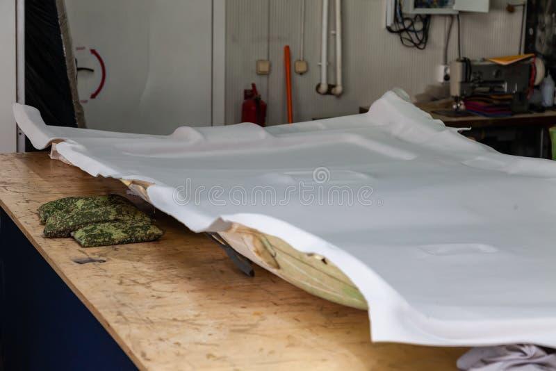 Forro de teto cinzento removido do carro para ajustar e apoiar com o material macio cinzento em uma tabela na oficina no fotografia de stock royalty free
