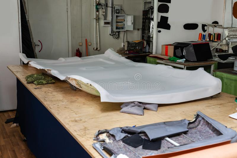 Forro de teto cinzento removido do carro para ajustar e apoiar com o material macio cinzento em uma tabela na oficina no fotos de stock
