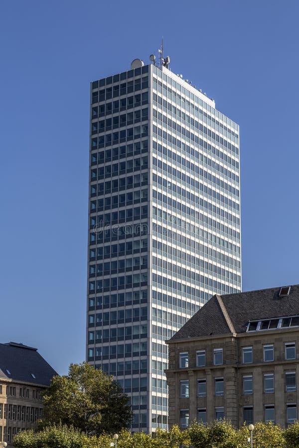 Fors av en kontorsbyggnad och gamla byggnader framme arkivbild