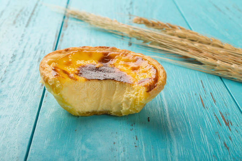 Fors för studio för sidosikt av det portugisiska ägget som är syrlig med en tugga och ett vete på wood bakgrund royaltyfri foto