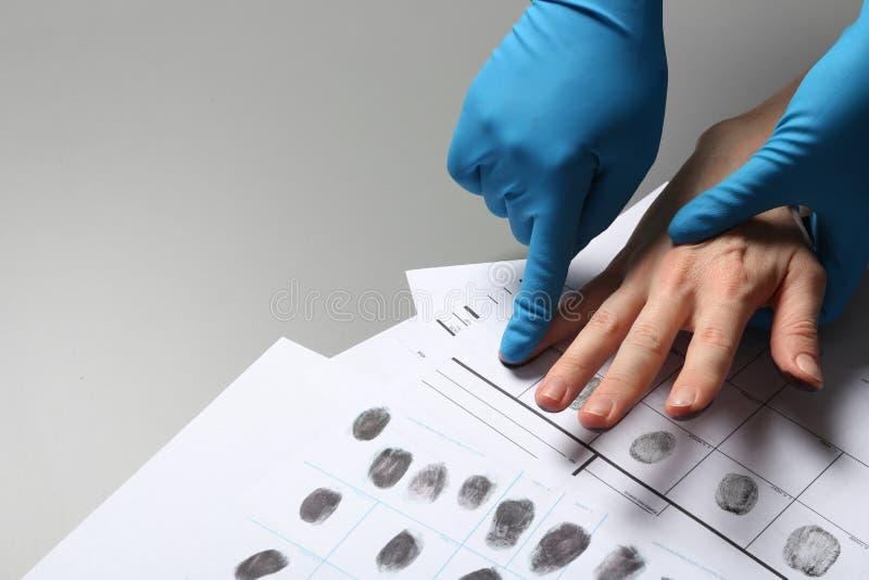 Forscher, der Fingerabdrücke des Verdächtigen auf grauer Tabelle, Nahaufnahme nimmt stockfotos