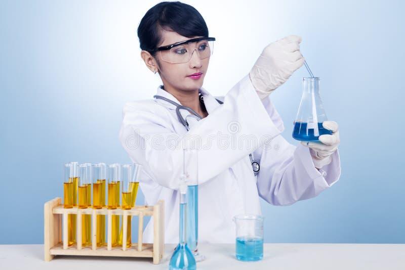 Forscher, der mit Chemikalie arbeitet stockbild
