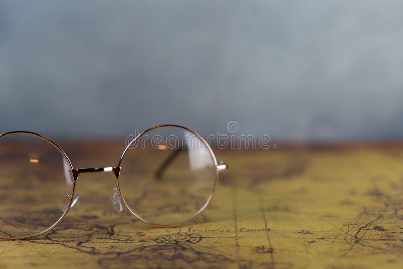 Forscher Glasses auf Weinleseweltkarte stockfotos