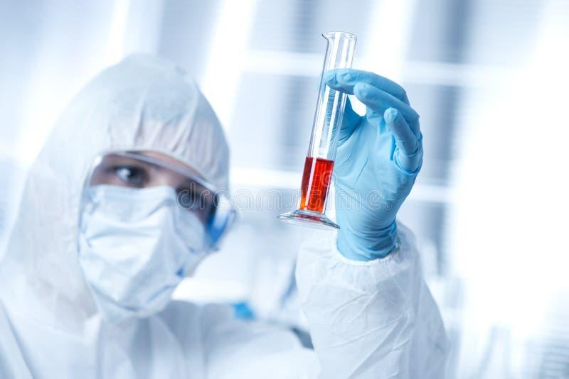 Forscher in hazmat Klage mit Reagenzglas lizenzfreie stockbilder