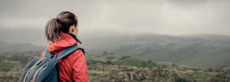 Forschermädchen, das in die Berge geht lizenzfreie stockbilder