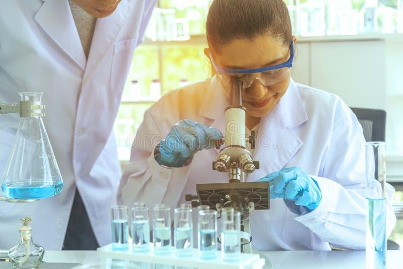 Forskare förklarar experiment, genom att avläsa mikroskopet i laboratoriumet fungera f?r laboratoriumforskare royaltyfri foto