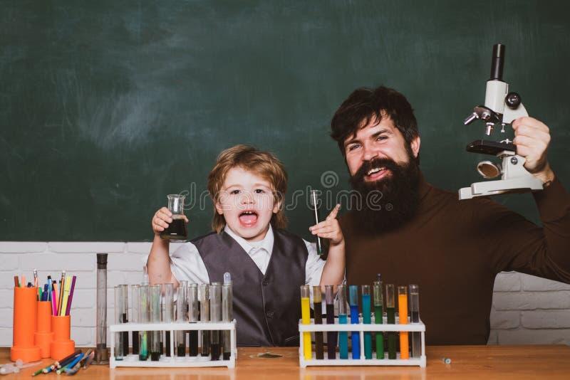 Forskare f?r liten unge som tj?nar kemi i skolalabb biologiexperiment med mikroskopet Mannen undervisar barnet Pappa och royaltyfri bild