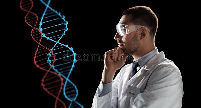 Forskare i skyddsglasögon som ser dna-molekylen royaltyfri foto
