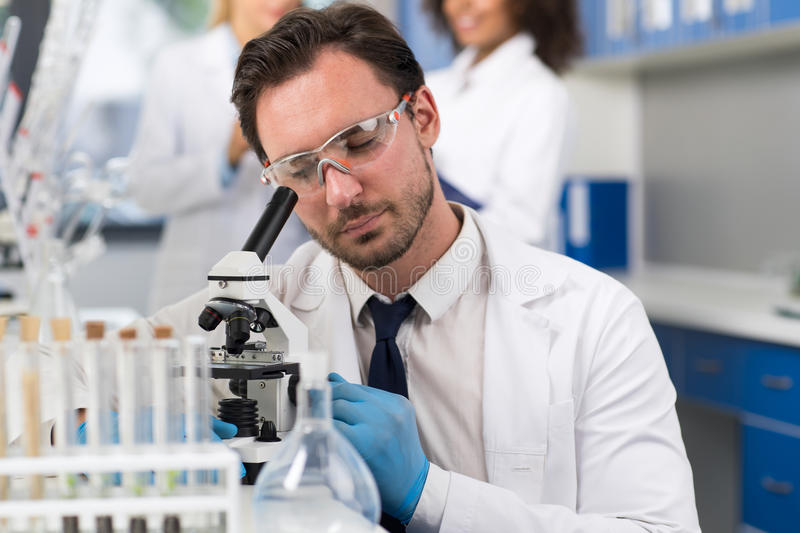 Forskare Looking Through Microscope i laboratorium, manlig forskare Doing Research Experiments arkivbild