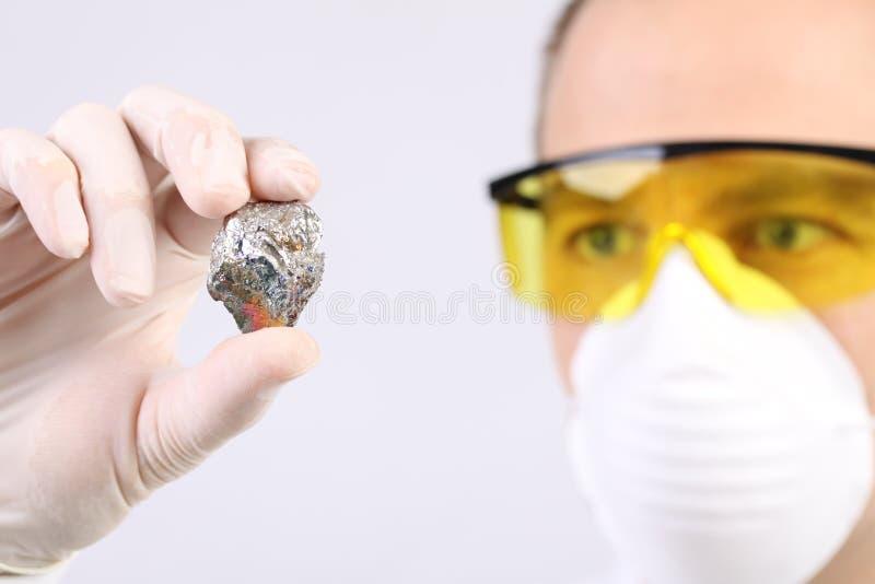 Forskare med en prövkopia av metall arkivbild