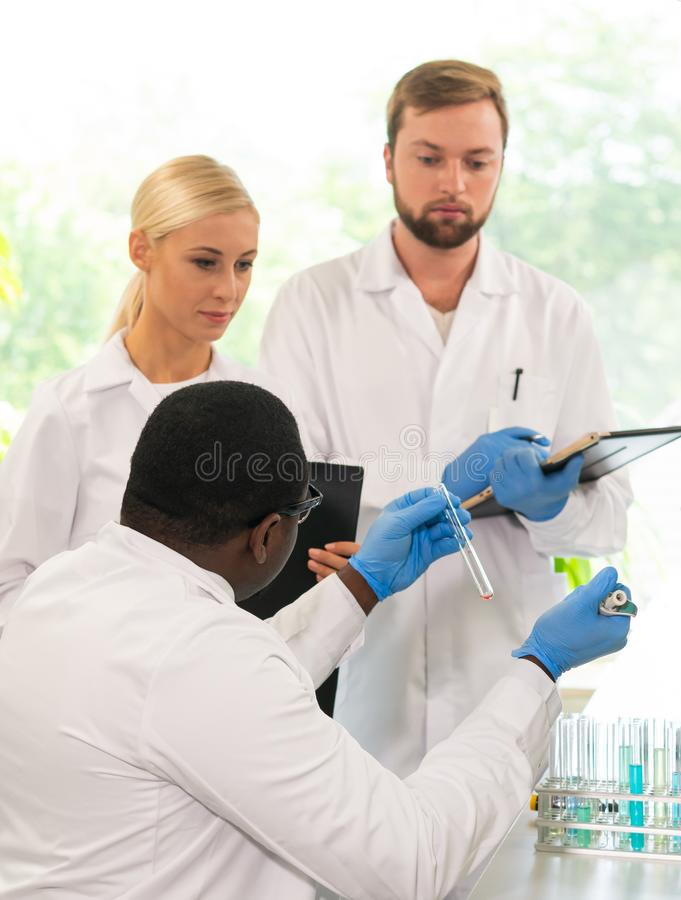Forskare och studenter som arbetar i labb Manipulera undervisande allmäntjänstgörande läkare för att göra blod som analyserar for arkivfoto