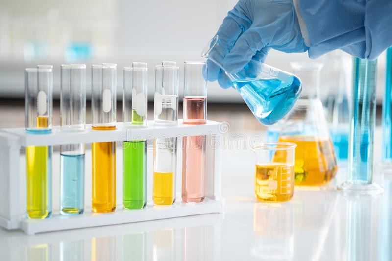 Forskare rymmer ett exponeringsglasrör i hand Att att förbereda och testa bestämda vikter royaltyfri foto