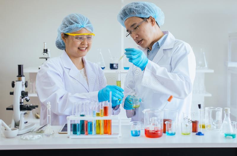 Forskare som arbetar sätta den medicinska kemikalieprövkopian i provrör på labbet tillsammans royaltyfria foton