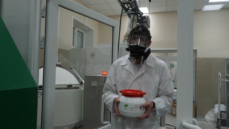 Forskare som bär den skyddande dräkten och bär en krus av giftlig flytande inom ett biohazardområde arkivfoton