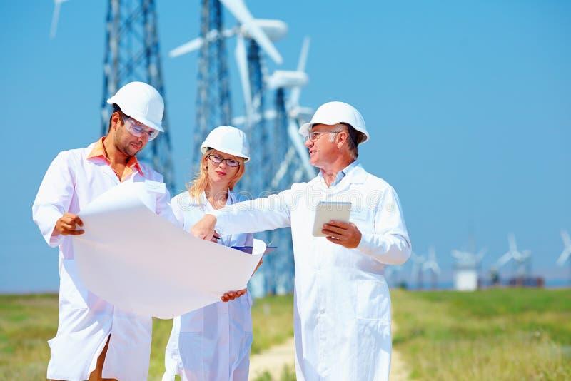 Forskare som diskuterar projekt på vindkraftstation arkivfoto