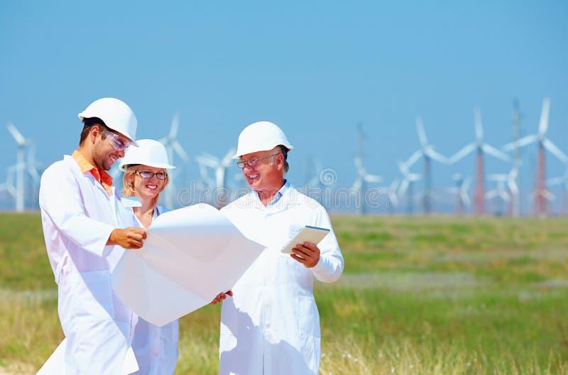 Forskare som diskuterar projekt på vindkraftstation arkivbilder