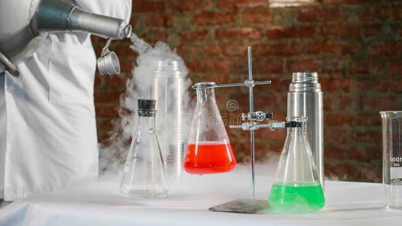 Forskare som häller vätskegasformigt grundämne i ståltermosflaska på laboratoriumet royaltyfria foton
