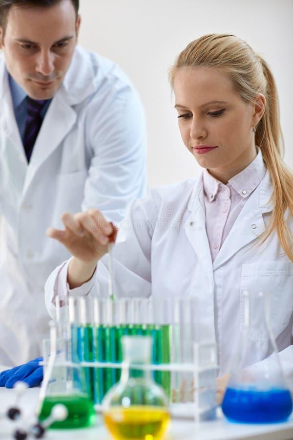 Forskare som kombinerar den kemiska flytanden genom att använda en pipett i prov arkivbilder