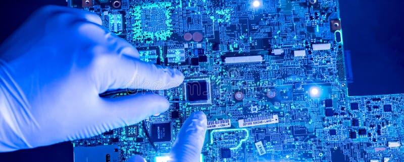 Forskarehänder i det forska universitetarbetet med chipen f för ny teknikdatorCPU royaltyfria foton