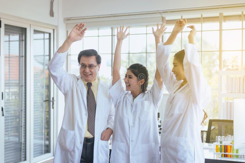 Forskarehandrais upp, grupp av mångfaldfolkteamwork i laboratorium, framgång- och resercharbete arkivfoto