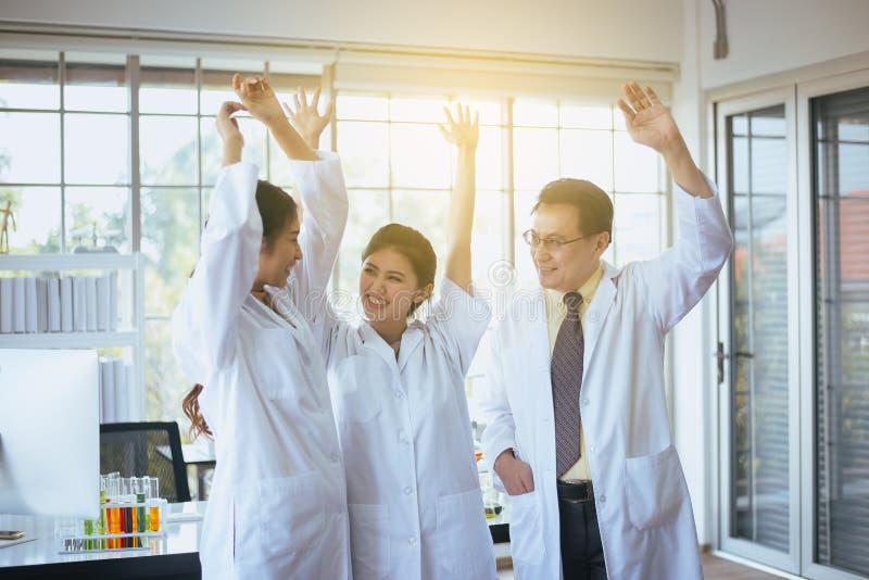Forskarehandrais upp, grupp av m?ngfaldfolkteamwork i laboratorium, framg?ng- och resercharbete arkivbilder